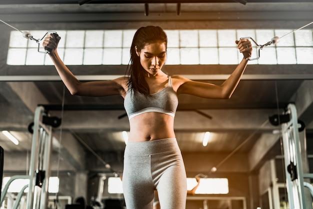A mulher nova da aptidão executa o exercício com a máquina do exercício no gym. fazendo exercícios de treino.