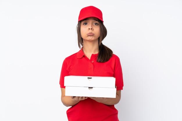 A mulher nova da entrega da pizza sobre a parede branca isolada mantém a palma unida. pessoa pede algo