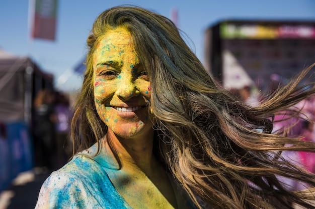 A mulher nova de sorriso cobriu sua face com a cor do holi que olha a câmera