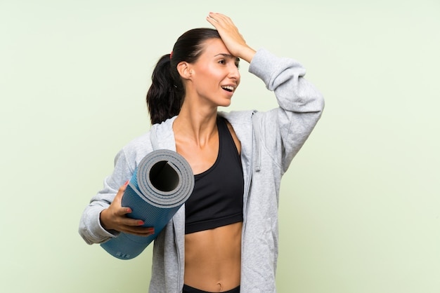 A mulher nova do esporte com esteira sobre a parede verde isolada realizou algo e pretendendo a solução