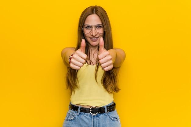 A mulher nova do gengibre do ruivo com o freckless com polegares levanta, elogios sobre algo, apoia e respeita o conceito.