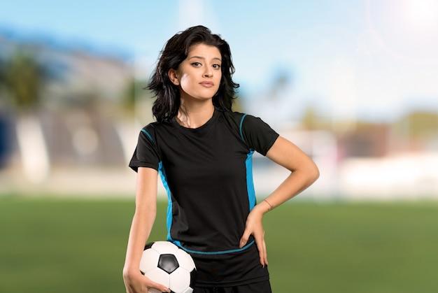A mulher nova do jogador de futebol que faz dúvidas gesticula ao levantar os ombros no ar livre