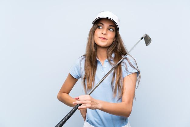 A mulher nova do jogador de golfe sobre a parede azul isolada que faz dúvidas gesticula ao levantar os ombros