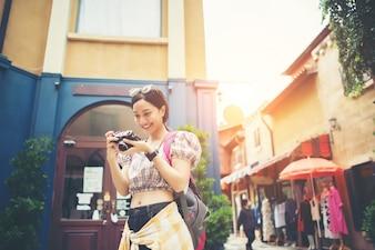 A mulher nova do moderno aprecia tirar a foto em urbano ao viajar.