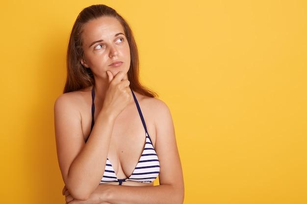 A mulher nova do nadador europeu isolada sobre a parede amarela, olha pensativa, olhando o espaço da cópia com expressão facial pensativa, veste o roupa de banho listrado.