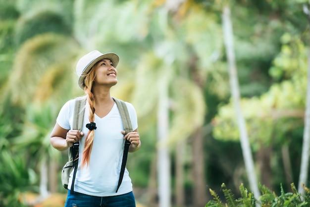 A mulher nova do turista com trouxa aprecia a natureza que olha afastado.