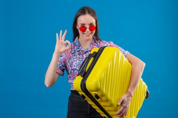 A mulher nova do viajante que veste óculos de sol vermelhos que guarda a mala amarela positiva e feliz que sorri fazendo está bem assina sobre a parede azul