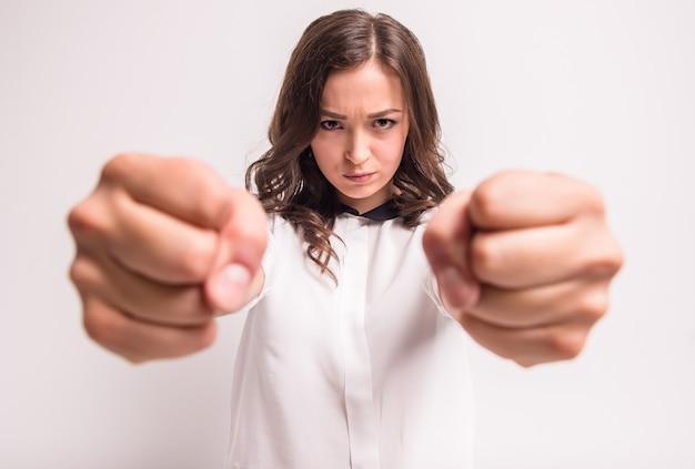 A mulher nova e irritada está apertando seus punhos na raiva.