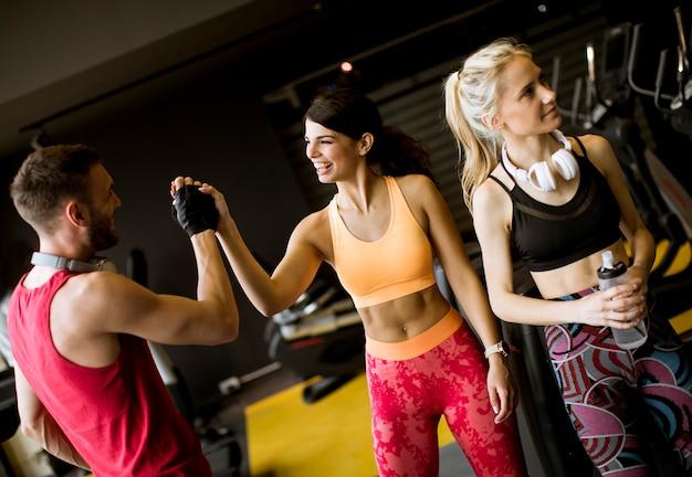 A mulher nova e o instrutor pessoal descansam no gym após o exercício