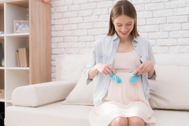 A mulher nova grávida prende sapatas para recém-nascido.