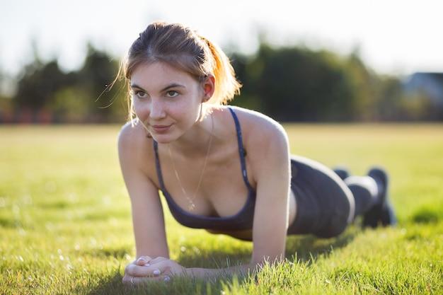 A mulher nova nos esportes veste o treinamento no campo no nascer do sol.