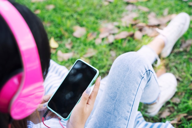 A mulher nova que usa a música móvel e escutando com os auscultadores no jardim com relaxa
