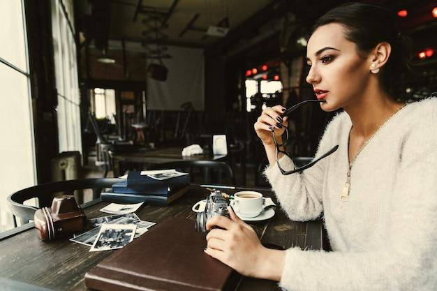 A mulher parece pensativa sentada à mesa com fotos antigas no café