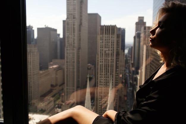 A mulher pensativa com uma túnica de seda preta se senta no peitorel da janela antes da bela paisagem urbana de nova york