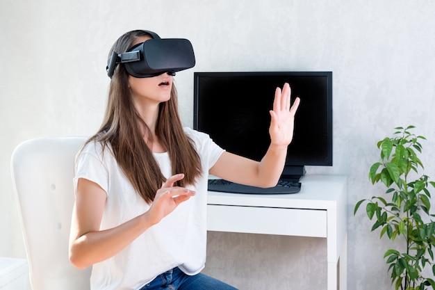 A mulher positiva de sorriso que veste a realidade virtual óculos de proteção auriculares, caixa do vr. conexão, tecnologia, nova geração, conceito de progresso. menina tentando tocar objetos em realidade virtual