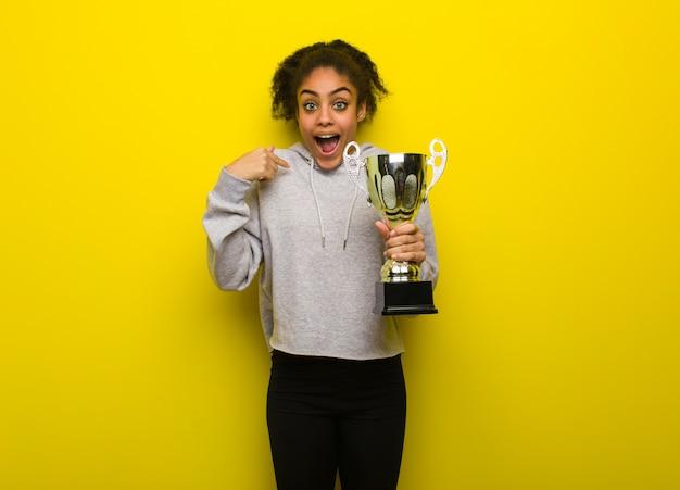 A mulher preta nova da aptidão surpreendida, sente bem sucedida e próspera. segurando um troféu.
