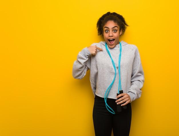 A mulher preta nova da aptidão surpreendida, sente bem sucedida e próspera. segurando uma corda de pular.