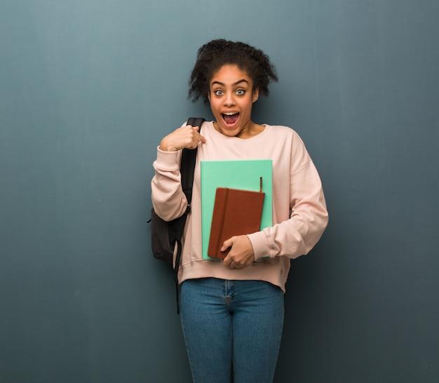 A mulher preta nova do estudante surpreendida, sente bem sucedida e próspera. ela está segurando livros.