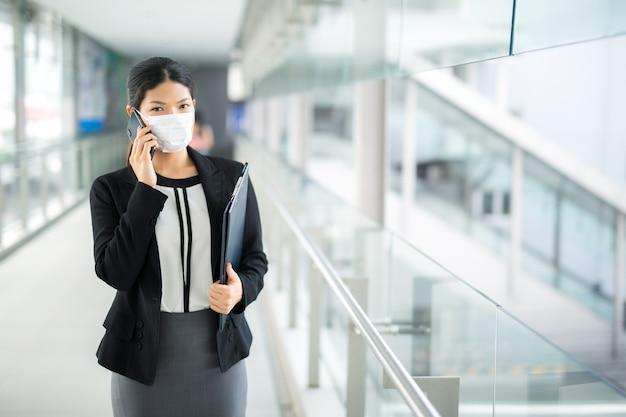 A mulher que anda com a proteção cirúrgica da máscara da máscara que anda e que chama o negócio que olha afastado nas multidões no trabalho da estação de trem do aeroporto comuta ao hospital.