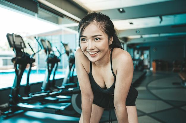 A mulher que está curvada e a mão trava os joelhos antes do exercício no gym.