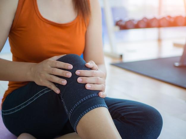 A mulher que faz a ioga do exercício em casa e que obtém o joelho feriu o problema. cuidados de saúde e con esporte