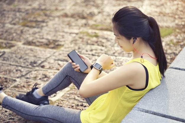 A mulher que guarda o telefone esperto conecta escuta a música ao fone de ouvido, dispositivo wearable da aptidão.
