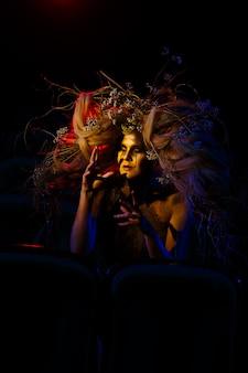 A mulher que interpreta um fantasma ou espírito no teatro está sentada entre as fileiras de cadeiras