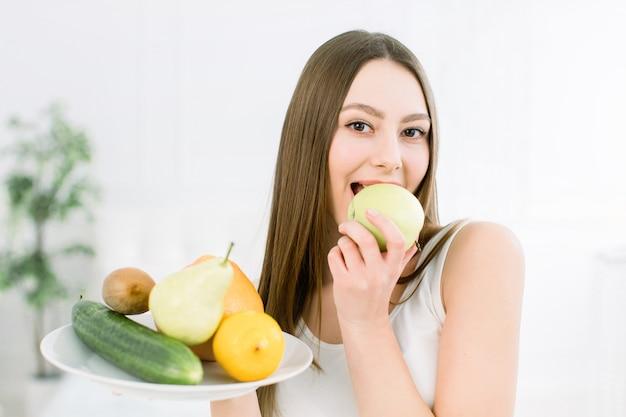 A mulher que mantém a variedade dos frutos serviu na placa branca contra o fundo claro.