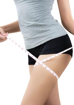 A mulher que mede seu coxa perde o peso e o conceito de corpo saudável no fundo branco.