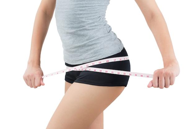 A mulher que mede seu quadril perde o peso e o conceito de corpo saudável no fundo branco.