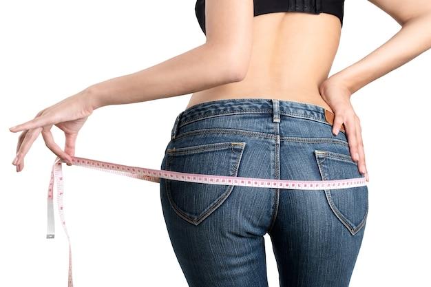 A mulher que mede sua parte inferior perde o peso e o conceito de corpo saudável no fundo branco.