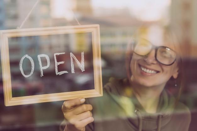 A mulher que pendura aberto assina dentro um café ou uma loja.