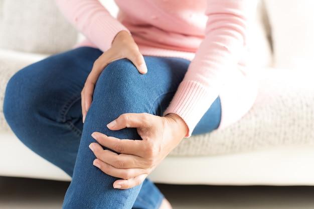 A mulher que senta a dor do joelho do sentimento e massageia seu joelho. conceito de saúde.
