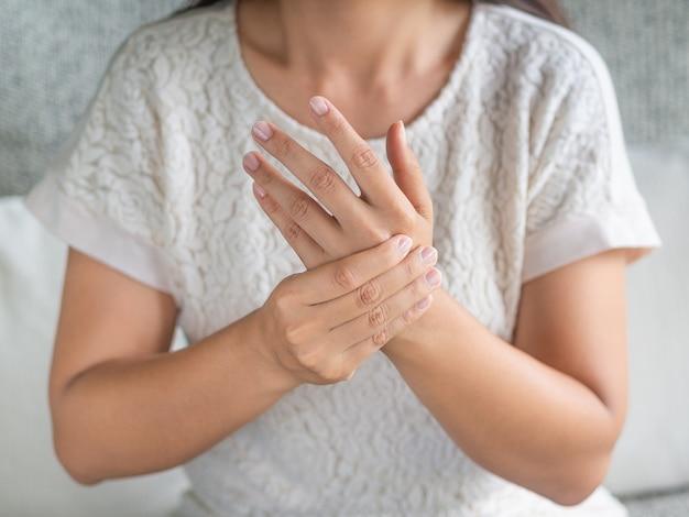 A mulher que senta-se no sofá prende seu pulso. lesão na mão