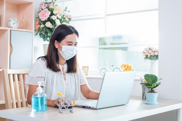 A mulher que usa uma máscara, atualmente trabalha em casa e faz compras online para a auto-quarentena durante o surto de doença do vírus corona (covid-19)