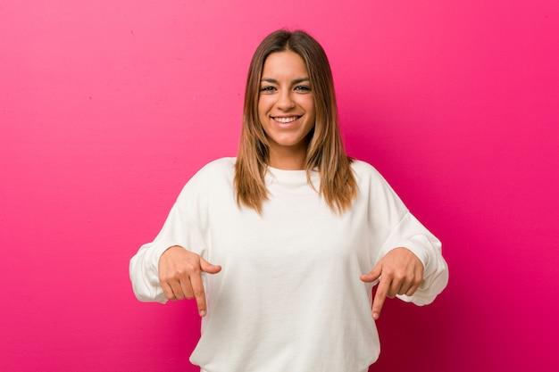 A mulher real carismática autêntica nova dos povos contra uma parede aponta para baixo com dedos, sentimento positivo.