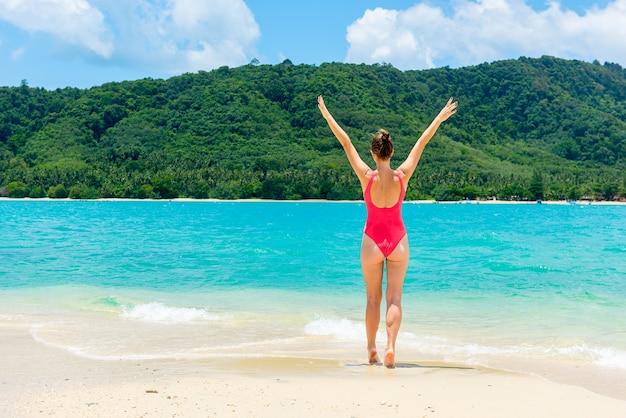 A mulher relaxa na praia, céu nebuloso azul da praia tropical. férias no paraíso. oceano b