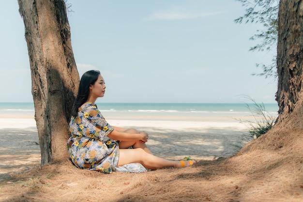 A mulher relaxa na praia sob o pinheiro na atmosfera calma.