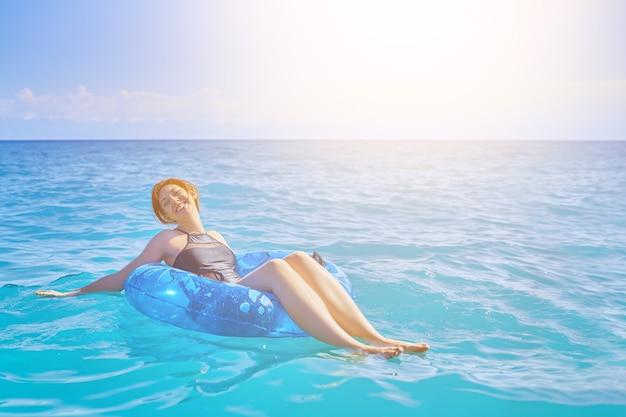 A mulher relaxa no anel inflável