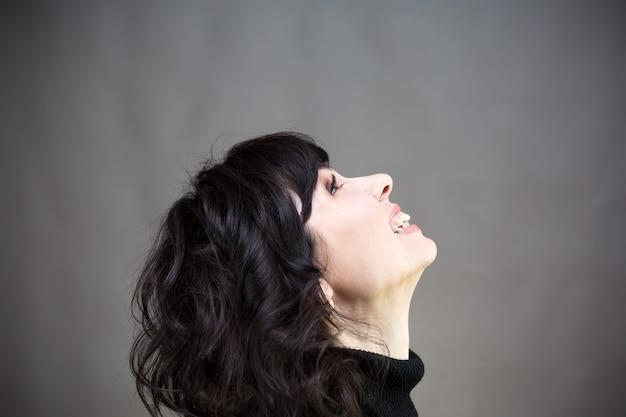 A mulher ri com a cabeça inclinada para trás. fundo cinza
