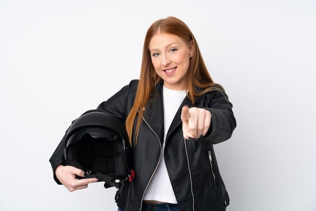 A mulher ruiva nova com um capacete da motocicleta sobre a parede branca isolada aponta o dedo para você com uma expressão confiante