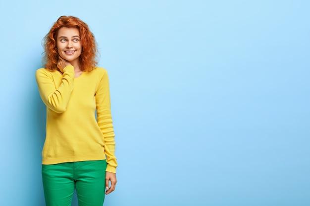 A mulher ruiva positiva tem um humor otimista da sorte, mantém a mão no pescoço, deixa o olhar triste e feliz de lado, usa uma roupa amarela e verde