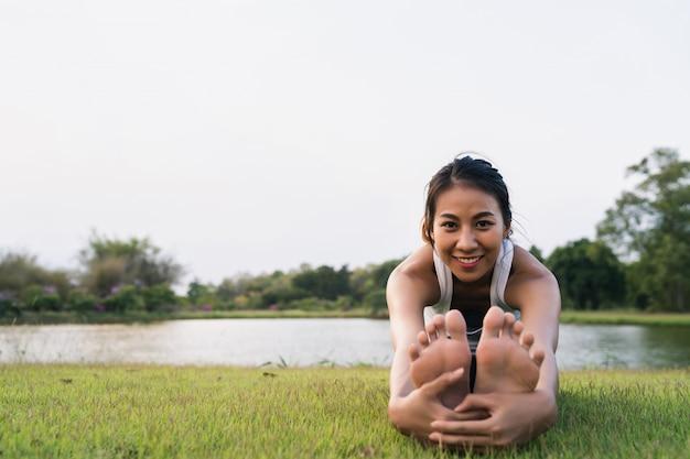 A mulher saudável do corredor asiático novo aquece o corpo que estica antes do exercício e da ioga