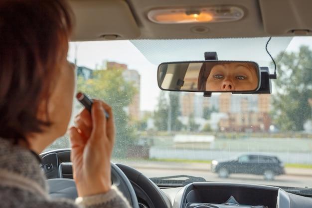 A mulher se olha no espelho retrovisor do carro e pinta os lábios