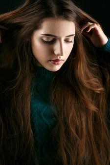 A mulher segura as mãos em longos cabelos castanhos