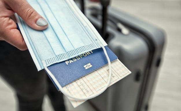 A mulher segura o passaporte com passagem de trem e a máscara médica como um elemento essencial na viagem no tempo pós-covid-19