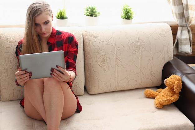 A mulher segura o portátil nos braços senta-se no sofá