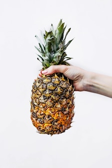 A mulher segura um abacaxi na mão