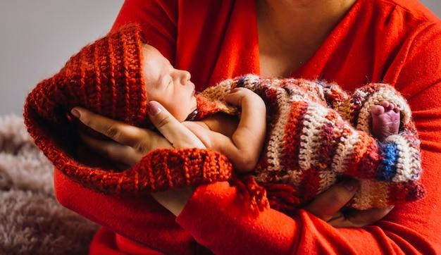 A mulher segura um bebê recém nascido em seus braços