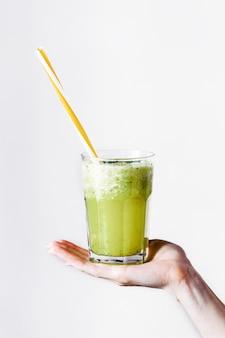 A mulher segura um copo com cocktail verde
